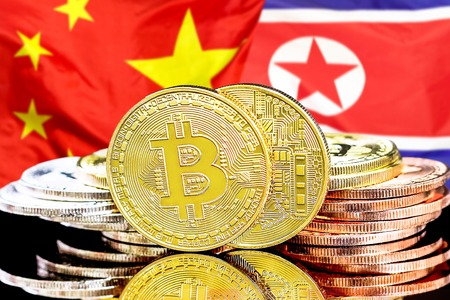 Concept for investors in cryptocurrency and Blockchain technology in the North Korea and China. Bitcoins on the background of the flag North Korea and China.
