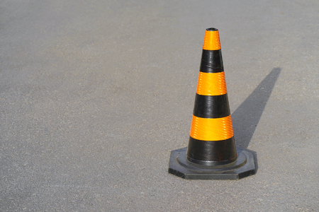 Traffic cone, with black and orange stripes on gray asphalt, copy space. Traffic cone on the road. Road cone on the asphalt.