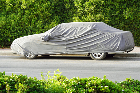 Car under a protective cover parked in the courtyard in sun weather, summer. The car on the side of the road under a protective cover on a green background of foliage bush Imagens