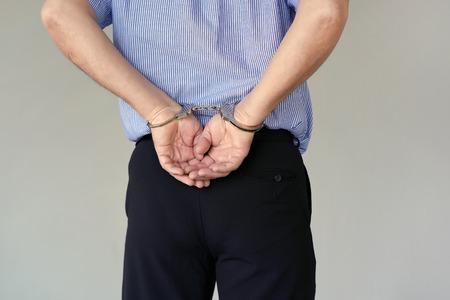 Zbliżenie. Aresztowany starszy mężczyzna skuty kajdankami ręce z tyłu na białym tle na szarym tle. Więzień lub aresztowany terrorysta, zbliżenie dłoni w kajdankach. Zamknąć widok