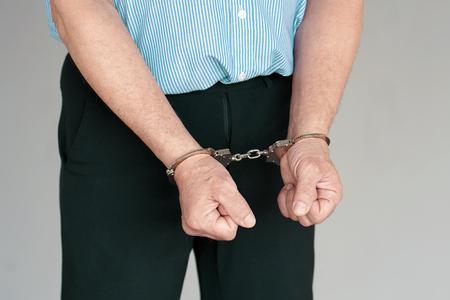 Fermer. Homme arrêté les mains menottées isolés sur fond gris. Prisonnier ou terroriste arrêté, gros plan des mains menottées. Banque d'images