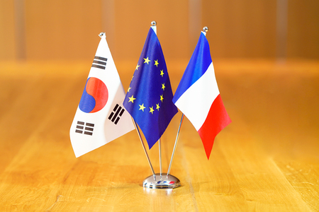 Three flags on the table. Flags of South Korea, European Union and France. Flags of South Korea, European Union and France on the table during a meeting of foreign ministers of France and South Korea.