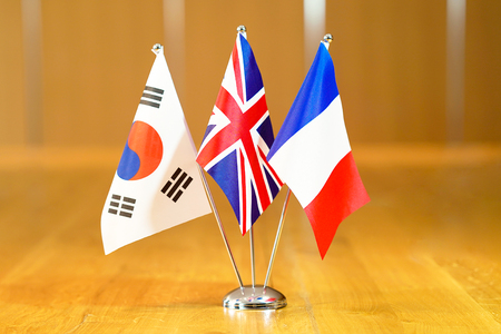 Three flags on the table. Flags of South Korea, United Kingdom and France. Flags of South Korea, France and UK on the table during a meeting of foreign ministers of South Korea, France and UK. Banco de Imagens - 124963716