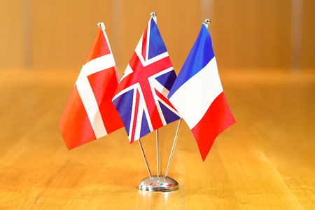 Three flags on the table. Flags of France, UK and Denmark. Flags of France, UK and Denmark on the table during a meeting of foreign ministers of France, UK and Denmark. Banco de Imagens