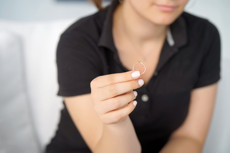Woman holding wedding engagement ring in hands, engaged girl doubts about marriage proposal, abandoned wife depressed after getting divorced, help to overcome breaking up, starting new life.
