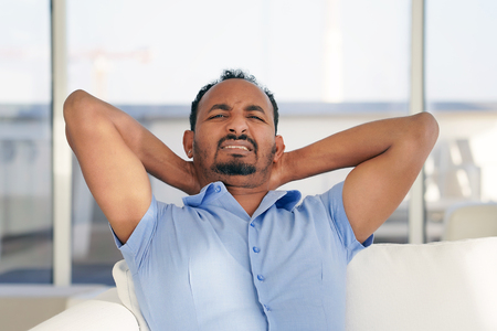 Man suffering from neck pain at home on couch. Males sense of fatigue, exhausted, stressed. African man massages her painful neck with her hands. The concept of body and health. Stock fotó