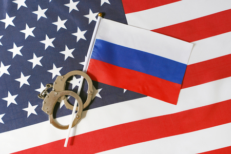 Russia flag in handcuffs on the background of the American flag. US sanctions against Russia.