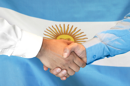 Business handshake on Argentina flag background. Men shaking hands and Argentina flag on background. Support concept
