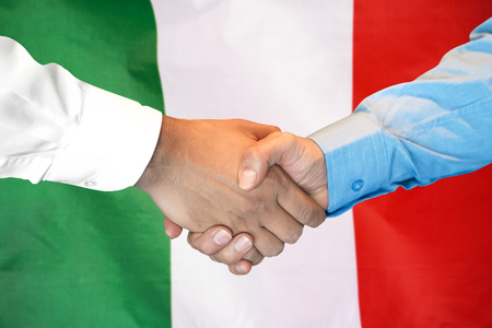 Business handshake on Italy flag background. Men shaking hands and Italy flag on background. Support concept 写真素材