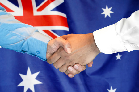 Business handshake on Australia flag background. Men shaking hands and Australia flag on background. Support concept