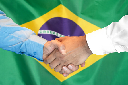 Business handshake on Brazil flag background. Men shaking hands and Brazil flag on background. Support concept 写真素材 - 124963746
