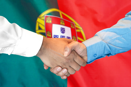 Business handshake on Portugal flag background. Men shaking hands and Portugal flag on background. Support concept