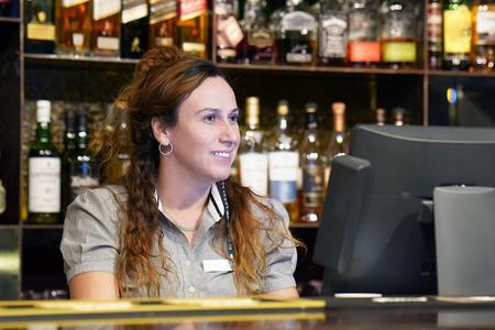 Female bartender registrating new order by cash-register. A waiterss restaurant worker registrating new order by cash-register. The concept of service. Banco de Imagens