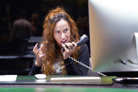 A woman-reception swears with the client of the hotel by phone. A woman is shouting into the phones phone. Funny facial expressions, emotions, reaction of perception, stress, gilding, nerves.