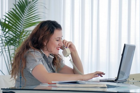 Close-up of an office worker. Woman secretary answering phone calls and talking with customers, she is sitting at her desk working.