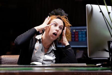 Hotel manager. A woman-reception shocked sitting in front of the monitor of computer. Funny face expression emotion feelings problem perception reaction, stress, fear Banco de Imagens