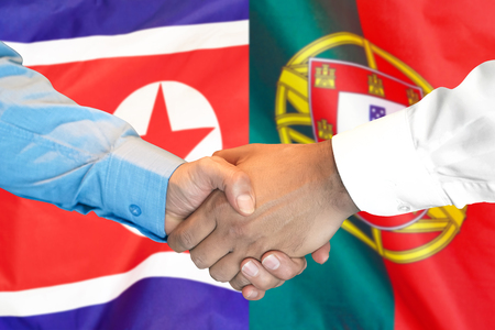 Business handshake on the background of two flags. Men handshake on the background of the Portugal and North Korea flag. Support concept