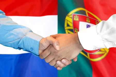 Business handshake on the background of two flags. Men handshake on the background of the Portugal and Dutch flag. Support concept