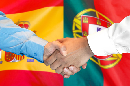 Business handshake on the background of two flags. Men handshake on the background of the Portugal and Spain flag. Support concept