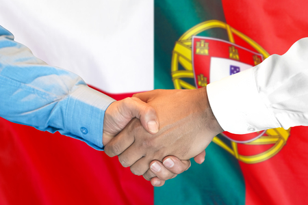 Business handshake on the background of two flags. Men handshake on the background of the Portugal and Poland flag. Support concept