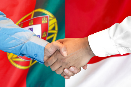Business handshake on the background of two flags. Men handshake on the background of the Portugal and Monaco flag. Support concept