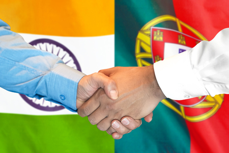 Business handshake on the background of two flags. Men handshake on the background of the Portugal and India flag. Support concept