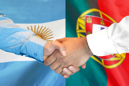 Business handshake on the background of two flags. Men handshake on the background of the Portugal and Argentina flag. Support concept