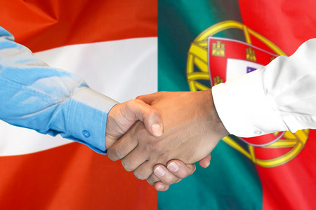 Business handshake on the background of two flags. Men handshake on the background of the Portugal and Austria flag. Support concept Zdjęcie Seryjne