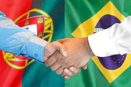 Business handshake on the background of two flags. Men handshake on the background of the Portugal and Brazil flag. Support concept
