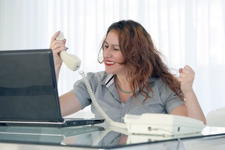 Close-up of an office worker swears with the client by phone. A woman is shouting into the phone's phone. Funny facial expressions, emotions, reaction of perception, stress, gilding, nerves.
