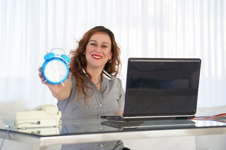 Red-haired woman holds an alarm clock in her hand in the workplace. female office worker holds an alarm clock in her hand at her desk. Woman holding a clock. Time management concept.