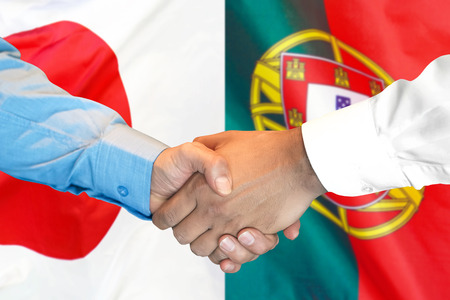 Business handshake on the background of two flags. Men handshake on the background of the Portugal and Japan flag. Support concept