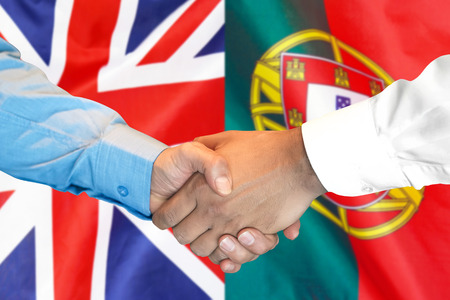 Business handshake on the background of two flags. Men handshake on the background of the Portugal and United Kingdom flag. Support concept Zdjęcie Seryjne