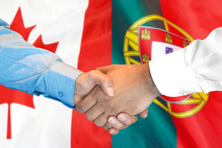 Business handshake on the background of two flags. Men handshake on the background of the Portugal and Canada flag. Support concept