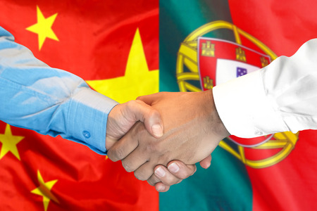 Business handshake on the background of two flags. Men handshake on the background of the Portugal and China flag. Support concept