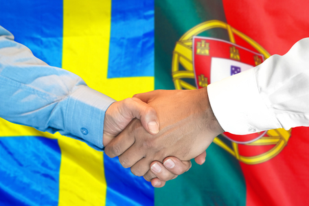 Business handshake on the background of two flags. Men handshake on the background of the Portugal and Sweden flag. Support concept Zdjęcie Seryjne