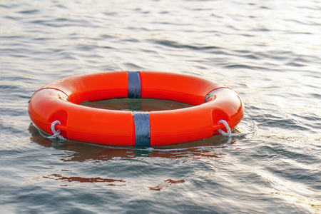 Red lifebuoy in sea on water. Life ring floating on top of water. Life ring in ocean.