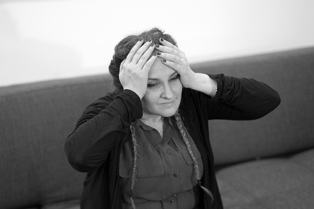 Black and white image woman suffering from headache migraine pain at home. Health problems, stress and depression. Female holds head with hand. Concept of health.