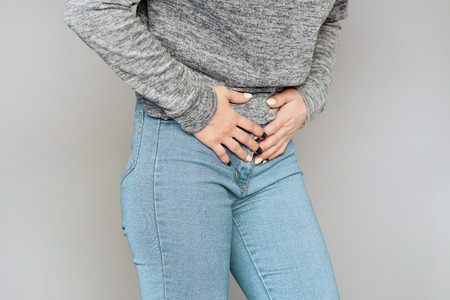 Woman having painful stomachache isolated on gray background. Chronic gastritis. Body And Health Care Concept.
