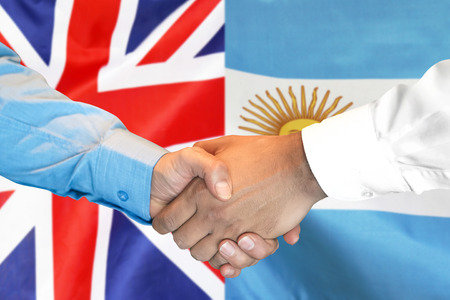 Business handshake on the background of two flags. Men handshake on the background of the United Kingdom and Argentina flag. Support concept