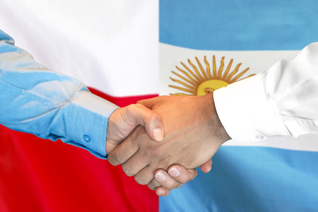 Business handshake on the background of two flags. Men handshake on the background of the Argentina and Poland flag. Support concept