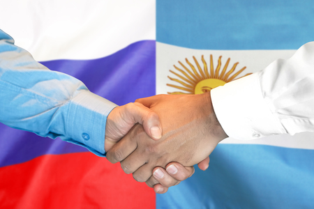 Business handshake on the background of two flags. Men handshake on the background of the Argentina and Russia flag. Support concept Zdjęcie Seryjne