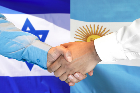 Business handshake on the background of two flags. Men handshake on the background of the Argentina and Israel flag. Support concept