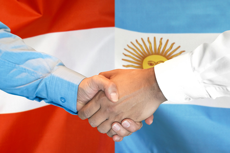 Business handshake on the background of two flags. Men handshake on the background of the Argentina and Austria flag. Support concept Zdjęcie Seryjne