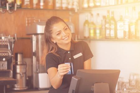 Bartender registrating new order by cash register. A restaurant worker registrating new order by cash-register. The waiter gives the card to the client. The concept of service. Toning Banco de Imagens