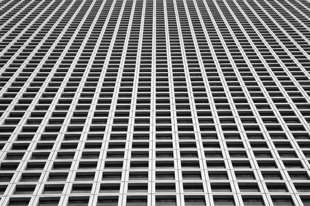 Black and white image of the outgoing perspective of the windows of the facade of a modern building. Glass grey square Windows of modern city business building skyscraper. Windows of a building, texture.