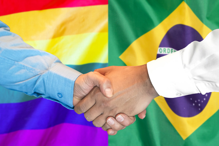 Business handshake on the background of two flags. Men handshake on the background of the Brazil and LGBT gay flag. Flag of tolerance. Support concept Zdjęcie Seryjne