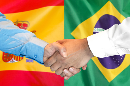Business handshake on the background of two flags. Men handshake on the background of the Brazil and Spain flag. Support concept