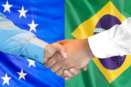 Business handshake on the background of two flags. Men handshake on the background of the Brazil and European Union flag. Support concept