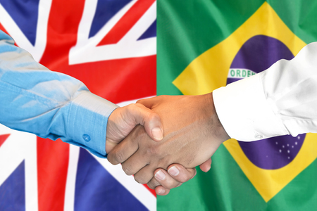Business handshake on the background of two flags. Men handshake on the background of the Brazil and United Kingdom flag. Support concept Zdjęcie Seryjne